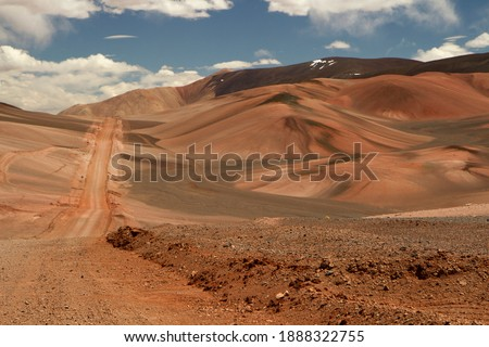 The dirt road high in the Andes mountains. Traveling along the route across the arid desert dunes and mountain range. The sand and death valley under a deep blue sky in La Rioja, Argentina.  Royalty-Free Stock Photo #1888322755