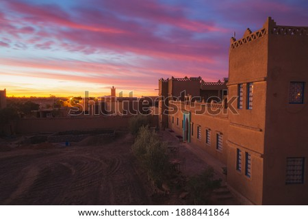 A vibrant sunrise or sunset over the village of Merzouga, the gateway to the Erg Chebbi desert dunes in Morocco. Royalty-Free Stock Photo #1888441864