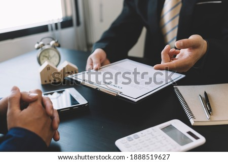 Home buyers meet and negotiate with real estate agents about renting or buying a home in the office. Royalty-Free Stock Photo #1888519627