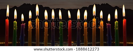Panoramic image with burning candles and night blurred electric lights of a city beneath mountains. Selective focus on flames of candles