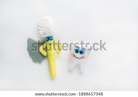 Happy tooth and toothbrush in cartoon style on white background. Handmade toys. Brushing teeth concept with funny characters. Flat lay, top view, copy space, soft focus.