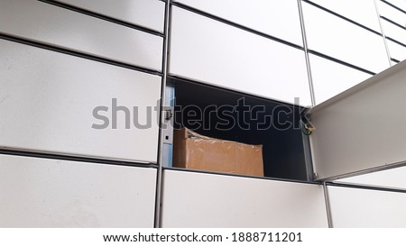 Courier Puts Cardboard Package Into Parcel Locker Royalty-Free Stock Photo #1888711201