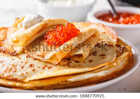 Traditional Russian Crepes Blini stacked in a plate with red caviar, fresh sour cream on light background. Maslenitsa traditional Russian festival meal. Russian food, russian kitchen. Close up. Royalty-Free Stock Photo #1888770925