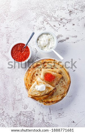 Traditional Russian Crepes Blini stacked in a plate with red caviar, fresh sour cream on light background. Maslenitsa traditional Russian festival meal. Russian food, russian kitchen. Top view. Royalty-Free Stock Photo #1888771681