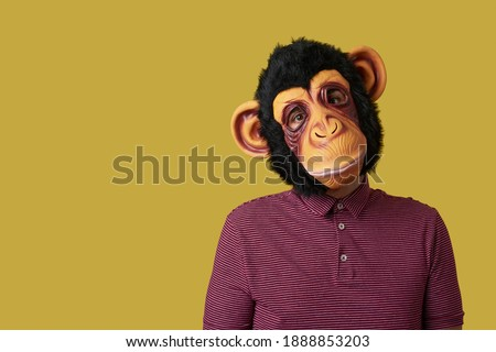 portrait of a man wearing a monkey mask on a yellow background with some blank space on the left Royalty-Free Stock Photo #1888853203