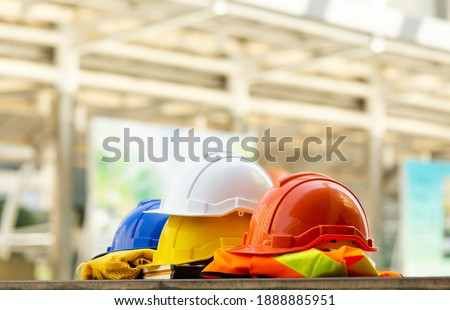 Close up Blue, yellow, white and red hard safety helmet hats for safety project of workman as engineering or project worker place on concrete floor city outdoor. Royalty-Free Stock Photo #1888885951