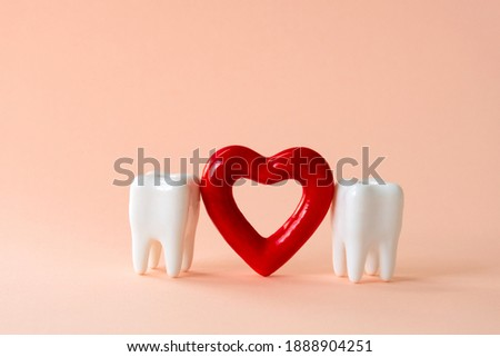Two teeth and red heart on a pastel background. Oral care and St. Valentine's day concept.