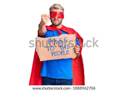 Young blond man wearing super hero custome holding power to the people cardboard banner annoyed and frustrated shouting with anger, yelling crazy with anger and hand raised