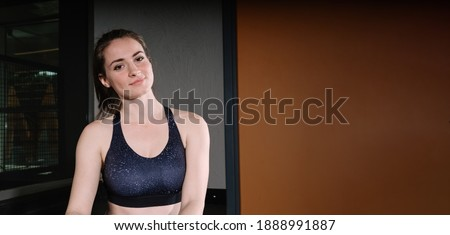 Beautiful young woman in the gym. The woman training in the gym poses for the camera. There is a writing area in the photo.