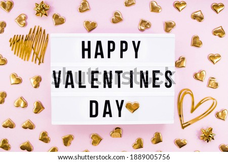 Stylish text frame lightbox with the inscription happy Valentine's day. Gold hearts all around. Foil balloons top view of Valentine's Day. Copyspace. Royalty-Free Stock Photo #1889005756