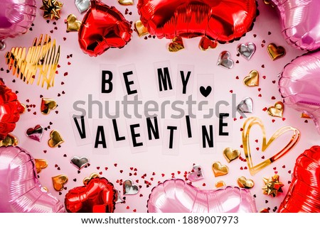 Stylish text frame with the inscription be my valentine. Pink, red and gold hearts all around. Foil balloons top view of Valentine's Day. Copyspace. Royalty-Free Stock Photo #1889007973