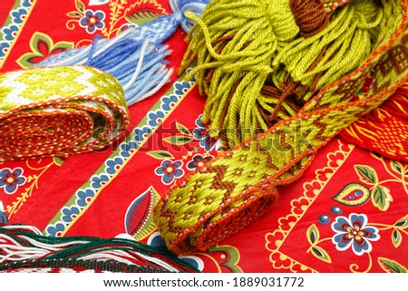 Multicolored ethnic background. Bright wool knits and hobbies. Handmade. Folk crafts. Ethnic folklore serving napkins made of thread on a black background. Twisted threads and knots. Ribbons and belts Royalty-Free Stock Photo #1889031772