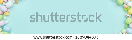 Happy Easter concept. Preparation for holiday. Easter candy chocolate eggs and jellybean sweets isolated on trendy pastel blue background. Simple minimalism flat lay top view copy space banner