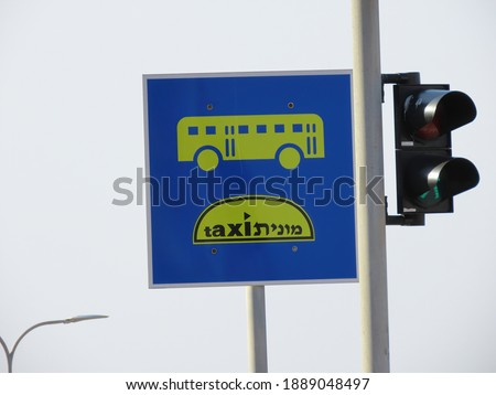 Road sign Public transport lane (buses and taxis) and traffic lights close-up in Haifa in Israel. The word taxi is written in two languages English and Hebrew. #1889048497