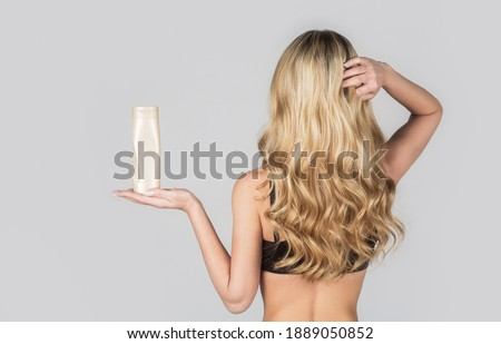 Beautiful blonde girl with a bottle of shampoos in hands. Girl with shiny and long hair. Woman long hair. Woman hold bottle shampoo and conditioner. Woman holding shampoo bottle. Royalty-Free Stock Photo #1889050852