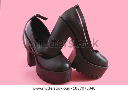 Womens platform shoes on a pink background. Punk, grunge, goth women shoes.