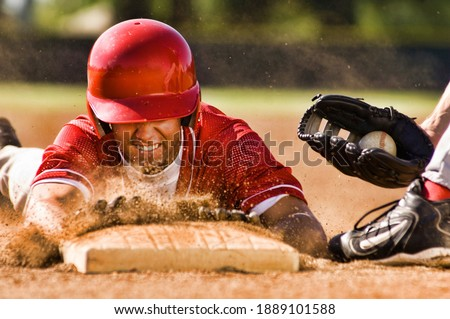 Portrait of man stealing base in baseball Royalty-Free Stock Photo #1889101588