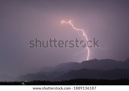 A picture of lightning in the sky and mountains