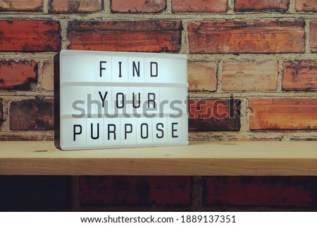 Find Your Purpose word in light box on brick wall and wooden shelves background Royalty-Free Stock Photo #1889137351
