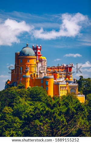 Famous historic Pena palace part of cultural site of Sintra against sunset sky in Portugal. Panoramic View Of Pena Palace, Sintra, Portugal. Pena National Palace at sunset, Sintra, Portugal.  Royalty-Free Stock Photo #1889155252