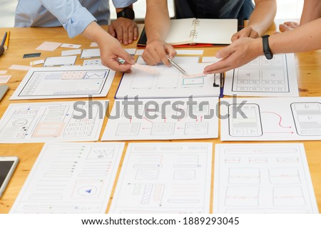 Graphic designers work together with UX UI designer planning application template layout framework for mobile phone computer mobile Royalty-Free Stock Photo #1889293045