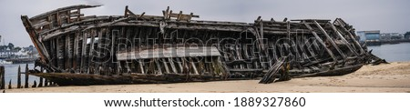 Stranded fishing boats on the beach. Historical wreck in France. Royalty-Free Stock Photo #1889327860