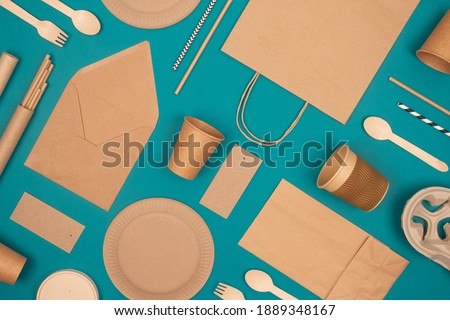Flat lay with eco-friendly tableware - kraft paper food packaging on green background. Street food paper packaging, recyclable paperware, zero waste packaging concept. Mockup, selective focus Royalty-Free Stock Photo #1889348167