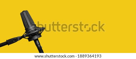 Professional microphone isolated on yellow background, podcast or website banner with copy space