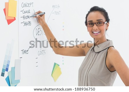 Designer writing on whiteboard and smiling at camera in creative office #188936750