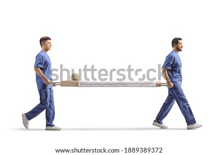 Full length profile shot of two male healthcare workers carrying an empty stretcher bed isolated on white background Royalty-Free Stock Photo #1889389372