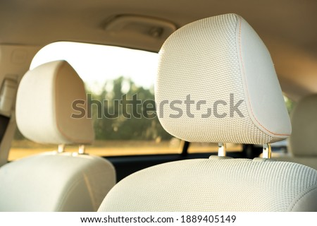 Closeup detail of light beige car headrests. Royalty-Free Stock Photo #1889405149