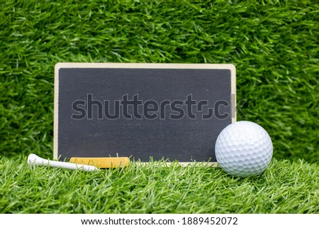 Chalkboard with golf ball and tee are on green grass