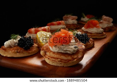 Savory Blini Pancakes with Cream Cheese and various toppings a delight for a party buffet or snack. Sweet Blini could be eaten for breakfast. Originated in Russia or Ukraine is a small round version. Royalty-Free Stock Photo #1889485504