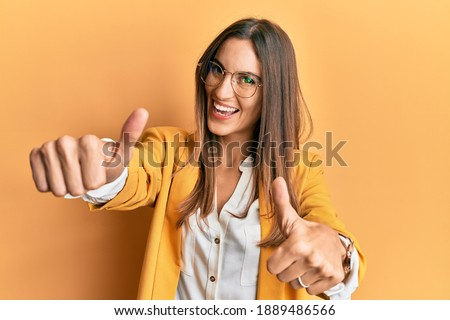 Young beautiful woman wearing business style and glasses approving doing positive gesture with hand, thumbs up smiling and happy for success. winner gesture.  Royalty-Free Stock Photo #1889486566