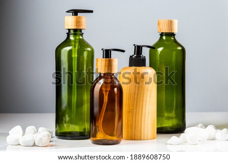 Set of green and brown glass cosmetic bottles with pumps and wooden elements for beauty products refill. Minimalistic bathroom accessories Royalty-Free Stock Photo #1889608750