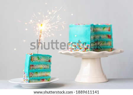 Slice of birthday cake with turquoise colored frosting and a sparkler Royalty-Free Stock Photo #1889611141