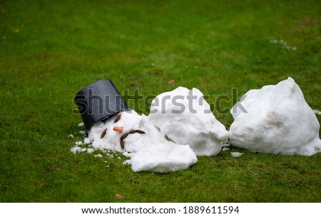 A melted snow man with a sad face as symbol of the end of the winter. Royalty-Free Stock Photo #1889611594