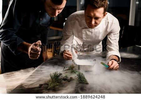 Two men chefs sprinkle on beautiful molecular cuisine dish decorated with pine branches in the smoke Royalty-Free Stock Photo #1889624248