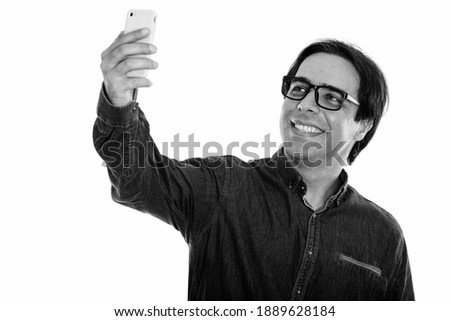 Studio shot of young happy Persian man smiling while taking selfie picture with mobile phone