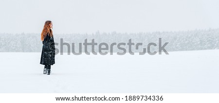 young teenage girl with long hair in black coat walking on show field. Winter outdoor photo
