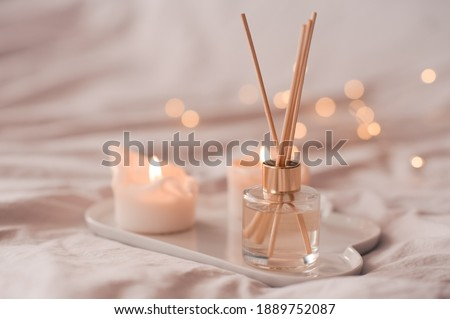 Home aroma fragrance diffuser with burning candles on white tray in bed over glowing lights close up. Cozy atmosphere. Wellness. Healthy lifestyle.  Royalty-Free Stock Photo #1889752087