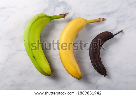 Process of ripening for banana showing a fresh green to yellow banana on left, an optimal ripened yellow banana in middle and a stale banana that turned dark brown due to enzymatic browning on right #1889851942