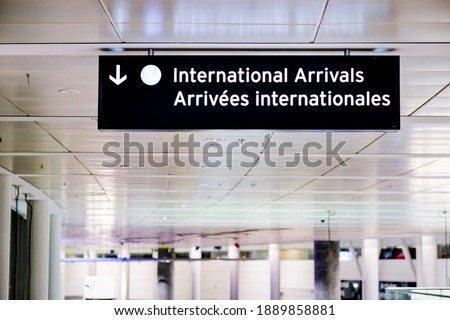 International arrivals sign board in english and french at airport terminal hall.  As coronavirus variant spreads through flights, government requires travellers to take a COVID-19 test upon arrival. Royalty-Free Stock Photo #1889858881