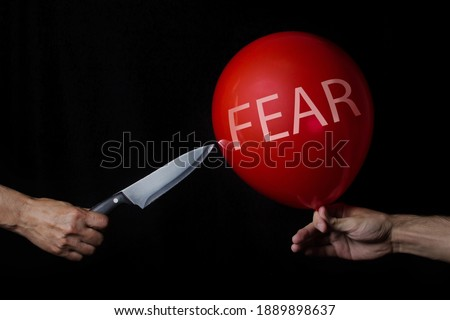 Fear. Getting rid of fears. Overcoming fear. Solution of problems. The knife pierces the red balloon. Royalty-Free Stock Photo #1889898637