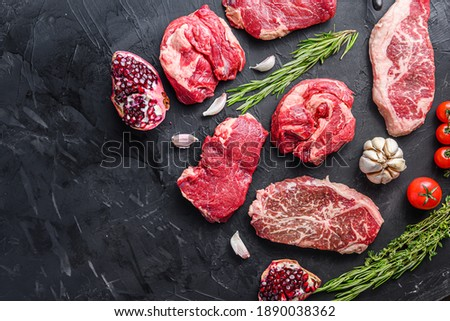 Alternative raw beef steak cuts with top blade, chuck roll and rump steak, with herbs and pomegranate top view, space for text Royalty-Free Stock Photo #1890038362