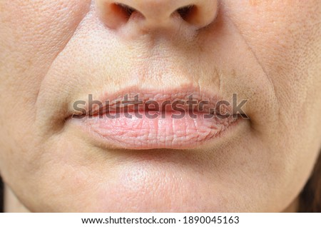 Closeup on the mouth of a middle-aged brunette woman with her mouth closed and a serious expression Royalty-Free Stock Photo #1890045163