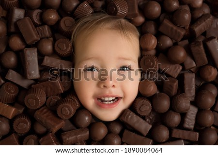 child's face close-up on a background of chocolate sweets. Excessive consumption of candy is harmful to health. Eating carbohydrates.  Chocolates with heart picture for valentine's da