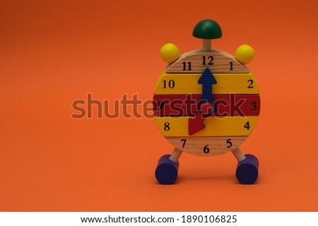 Children's, toy, wooden alarm clock isolated on an orange background. The clock shows 7 o'clock. Copy space Royalty-Free Stock Photo #1890106825