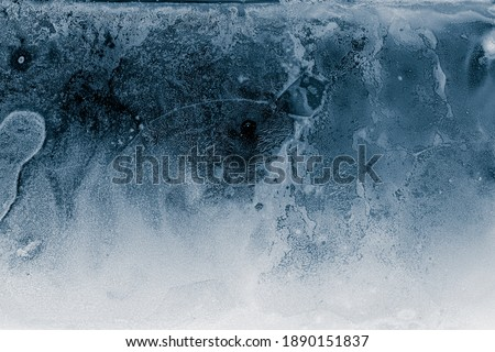 Ice texture background. Textured cold frosty surface of ice block on dark background.