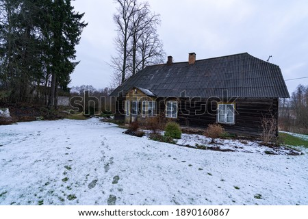 Old traditional wooden farm house with snowy frozen garden. Award winning garden during winter season. No sunlights. Home of the year. Traditional farmstead in rural area of Estonia near Polva
